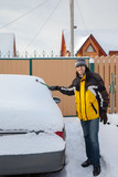 A man cleaning off the car after snow flurry poster