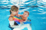 Little baby boy and his mother learning to swim in an indoor swi