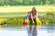 Leinwanddruck Bild - Adorable little girl and her mom playing with paper boats in a r