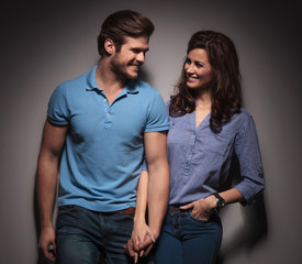 fashion couple leaning on a grey wall while holding hands