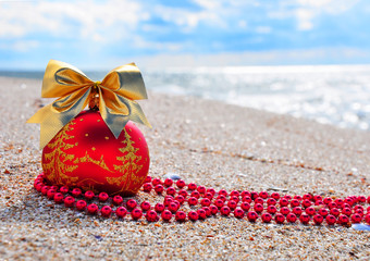 Red christmas bauble with golden bow on the sand