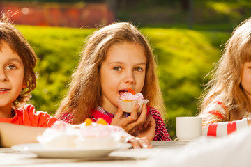 Close up view of kids drinking tea with cupcakes