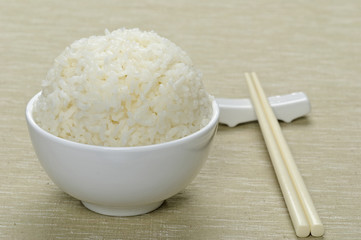White steamed rice in ceramic bowl and chopsticks