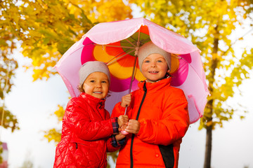 Boy and girl hold umbrella together under rain