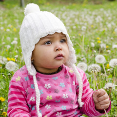 Child girl in meadow with dandelions
