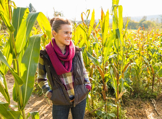 Happy woman standing in cornfield and looking on copy space