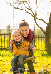 Portrait of smiling mother and child on swing