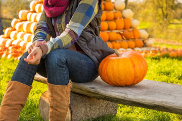 Closeup on happy young woman sitting with pumpkin