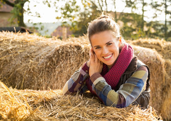Portrait of smiling young woman near haystack