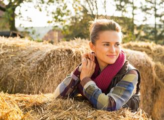 Happy young woman near haystack