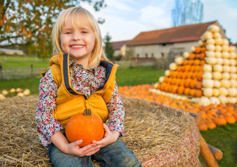 Portrait of happy child sitting on haystack with pumpkin