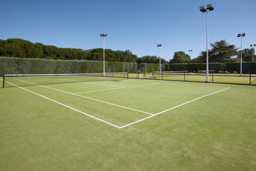 Tennis court with lamps and pine forest