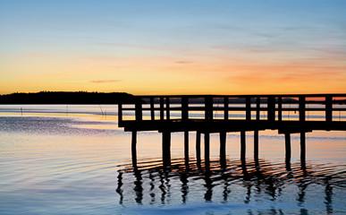 Molo di legno sul lago al tramonto