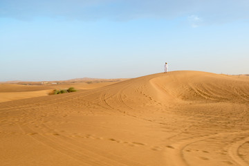Photo of local resident standing on a dune of a desert in the Un