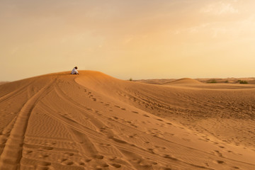 Photo of local resident praying on a dune of a desert in the Uni