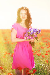 Beautiful young woman with flowers in poppy field