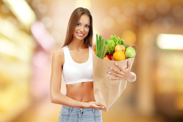 Shopping concept. Beautiful young woman with vegetables and