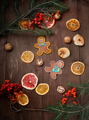 dried fruits and gingerbread painted on dark wooden background