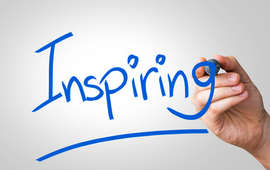 Inspiring hand writing with a blue mark on a transparent board