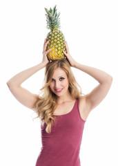 Frau hält eine Ananas auf dem Kopf