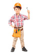 Cute little boy wearing working clothes and holding a wrench