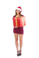 Festive brunette smiling at camera offering gift