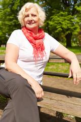 Seniorin sitzt auf Bank im Park