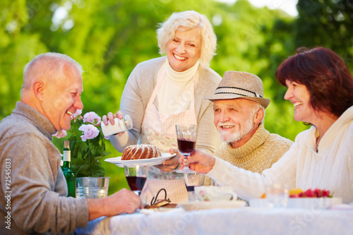 Gruppe Senioren feiert Geburtstag im Garten - 72545033