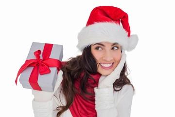 Surprised brunette in santa hat holding gift