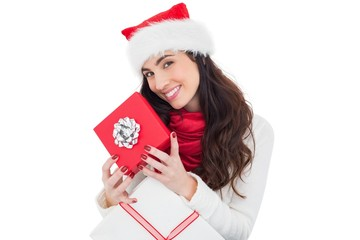 Smiling brunette holding christmas gifts