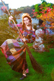 Fashionable in boho style girl holding broom poster