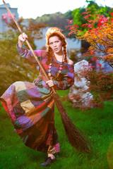 Fashionable in boho style girl holding broom