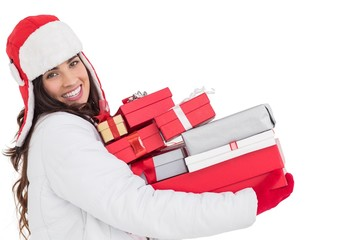 Festive brunette in winter clothes holding many gifts
