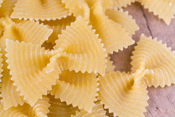 farfalle raw pasta on wooden table
