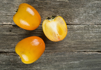 persimmons on wooden surface