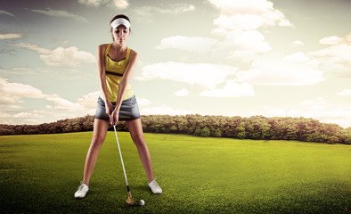 Golf player woman putting ball into hole on green field
