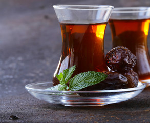 Turkish tea in traditional glass with sweet dates