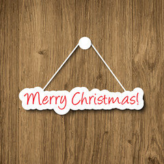 Merry Christmas sign hanging on a wood plank