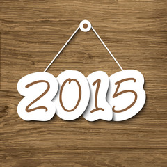 2015 sign hanging on a wood plank