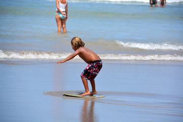 niño rubio practicando bodyboard