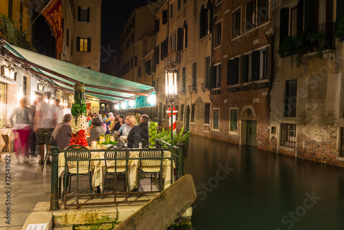 Night view of canal and restaurant in Venice, Italy