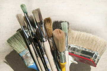 Bunch of various used paintbrushes on canvas background