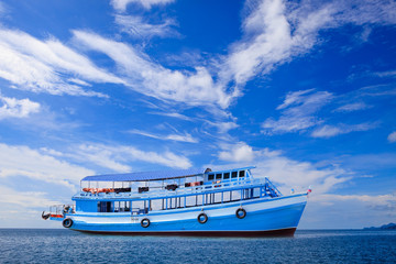 passenger wooden boat floating on blue sea water with beautiful