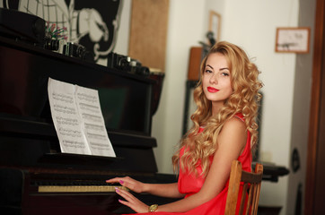 Beautiful young woman sitting at the piano in the room