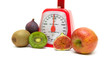 Ripe fruits and kitchen scales isolated close up on white backgr