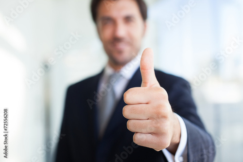 Businessman giving thumbs up - 72556208