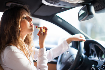 Woman applying make-up while driving