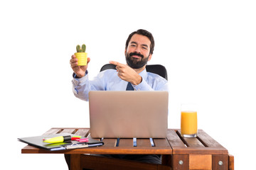 Businessman in his office holding cactus