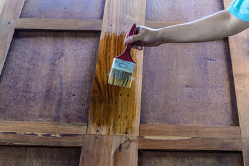 The carpenter is painted beautiful wood doors.