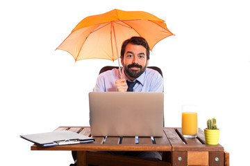 Businessman in his office holding an umbrella